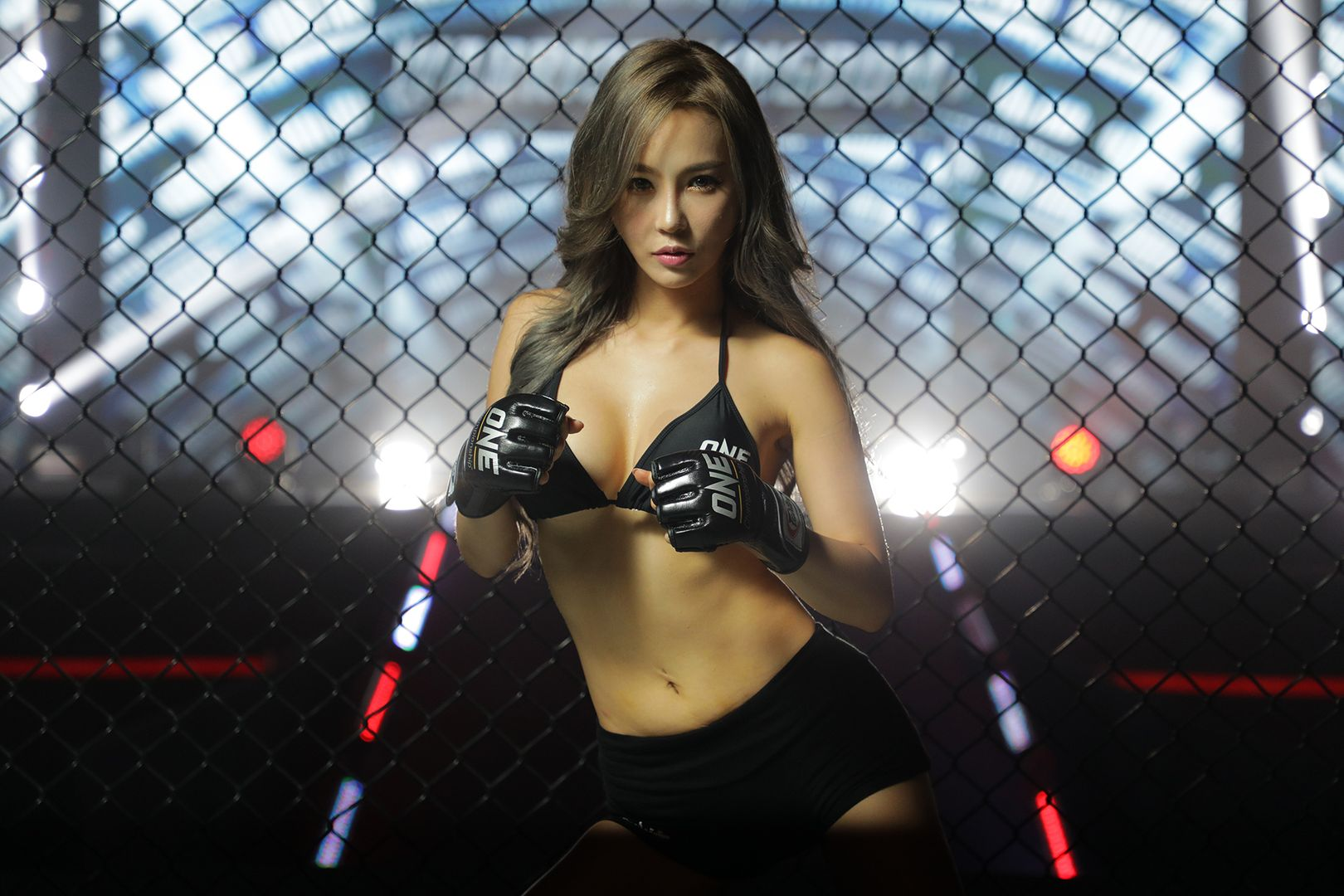 ONE Championship ring girl DJ Jina poses inside the cage and in front of the entrance way
