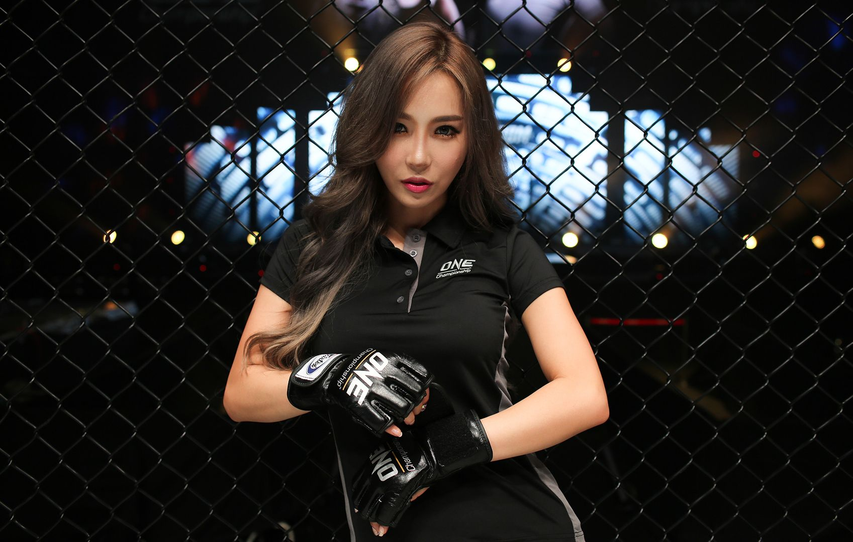 ONE Championship ring girl DJ Jina wears a ONE shirt and wears mixed martial arts gloves