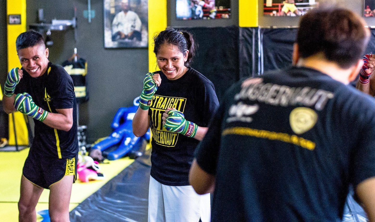 A person smiles while training Muay Thai at the old Juggernaut Fight Club