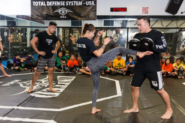 Ken Lee, Angela Lee, and Christian Lee demonstrate martial arts techniques to students at United MMA