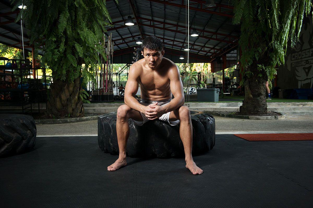 Russian lightweight mixed martial arts star Timofey Nastyukhin sits on a tire at Tiger Muay Thai in Phuket, Thailand