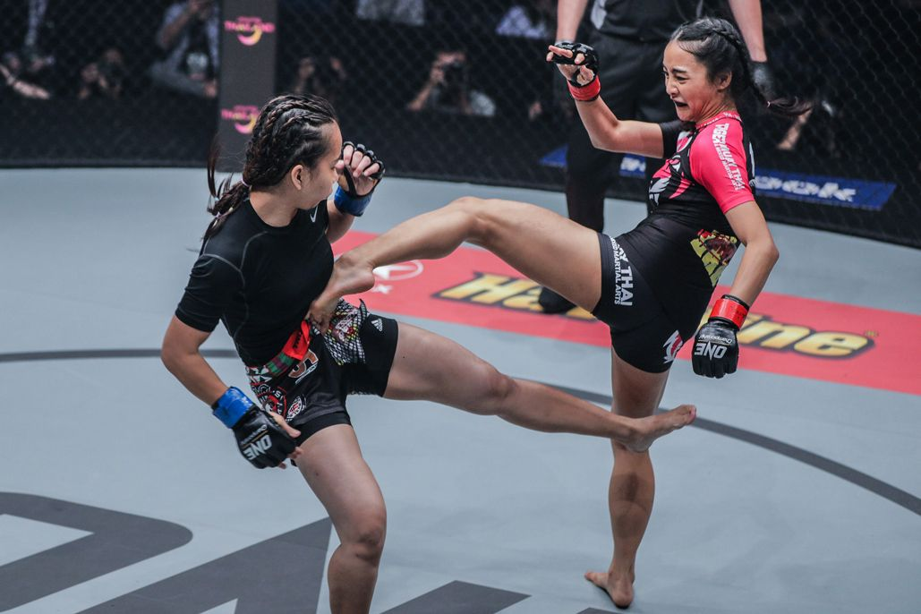 Thai mixed martial artist Rika Ishige connects with a body kick on Nita Dea