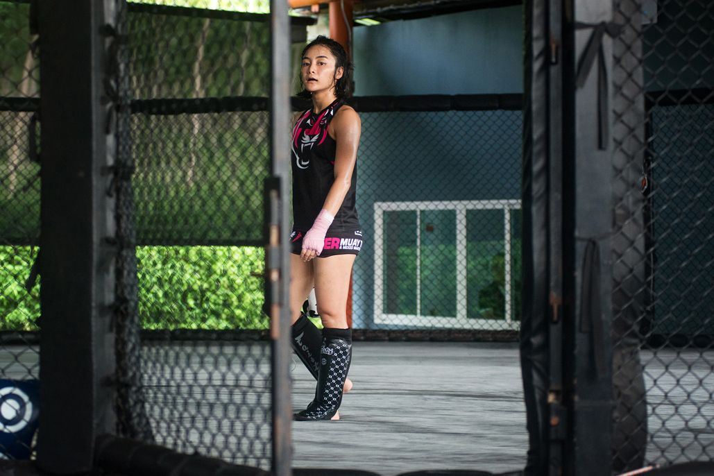 Rika Ishige stands in the cage in her shin guards
