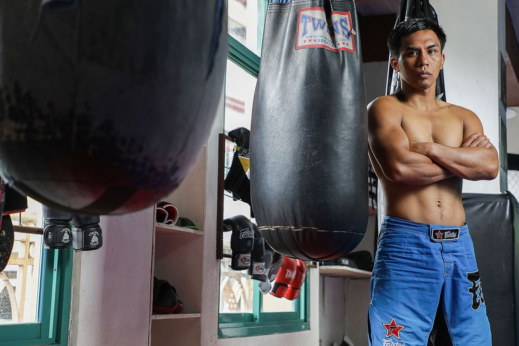 Kevin Belingon stands near heavy bags at Team Lakay