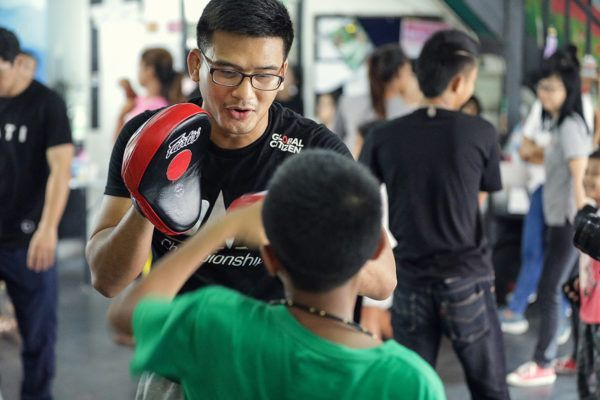 Thai MMA fighter Shannon Wiratchai holds pads for a child