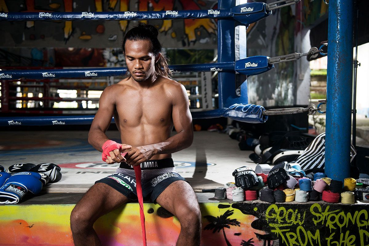 Malaysian martial artist Muhammad Aiman wraps his hands in red