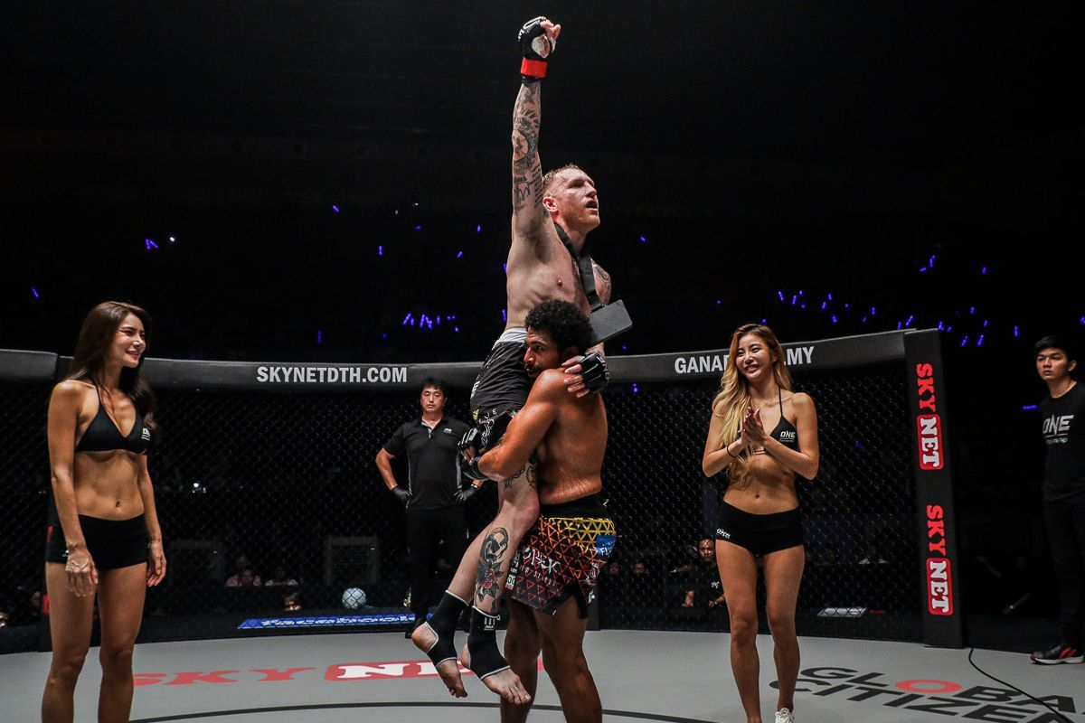 Australian Muay Thai fighter Elliot Compton raised in the air following his big win