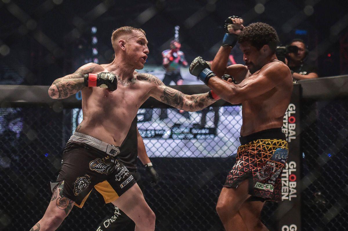 Australian Muay Thai Fighter Elliot Compton throws an uppercut at Matthew Semper's face