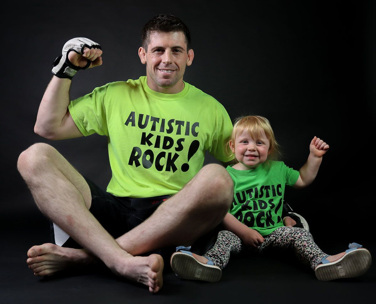American MMA fighter Tyler McGuire poses with his daughter in their Autism Rocks shirts