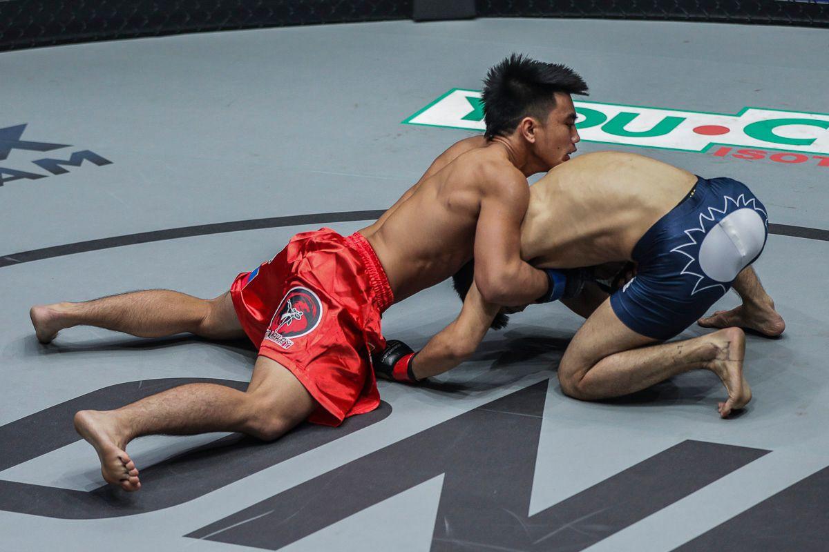 Joshua Pacio defends a takedown against Yoshitaka Naito