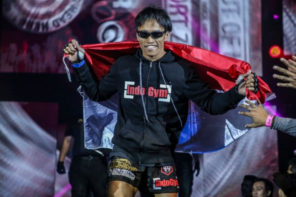 Indonesian MMA fighter Sunoto carries the Indonesian flag to the cage