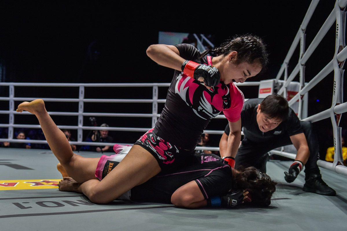 Thai mixed martial atist Rika Ishige punches her opponent with ground and pound