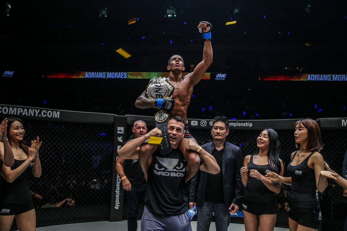 ONE Flyweight World Champion Adriano Moraes is raised upon his cornerman's shoulders