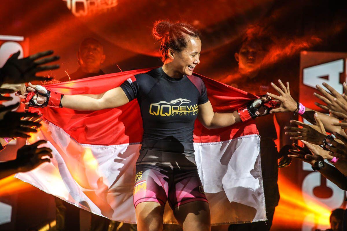 Indonesia's Priscilla Hertati Lumban Gaol walks to the ring with the flag