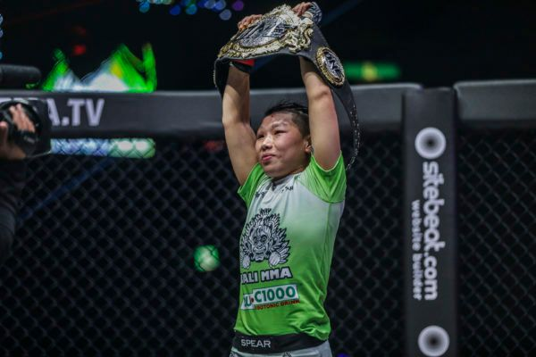 Xiong Jing Nan proudly raises the ONE Women's Strawweight World Championship belt