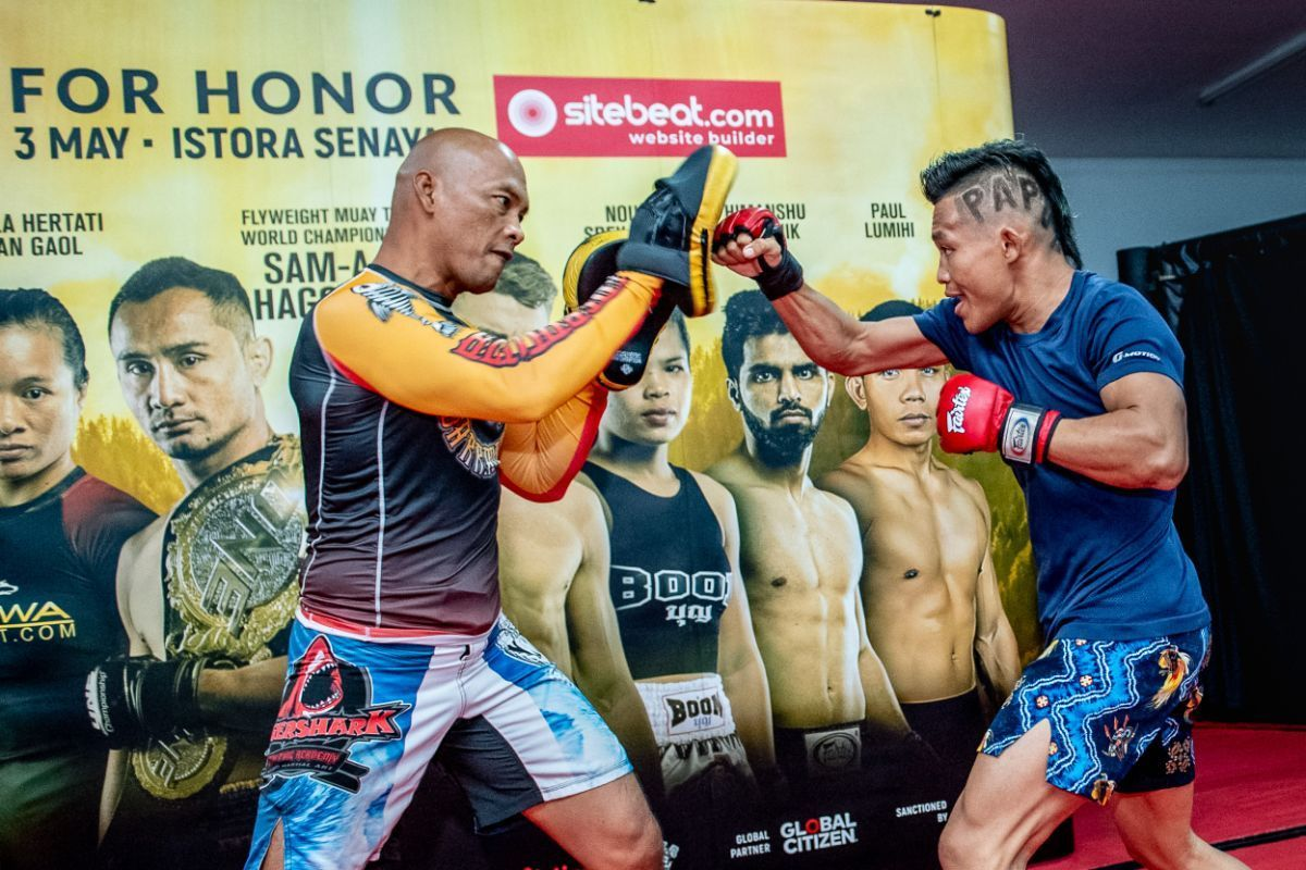Tigershark Fighting Academy head coach Zuli Silawanto holds focus mitts for Adrian Mattheis