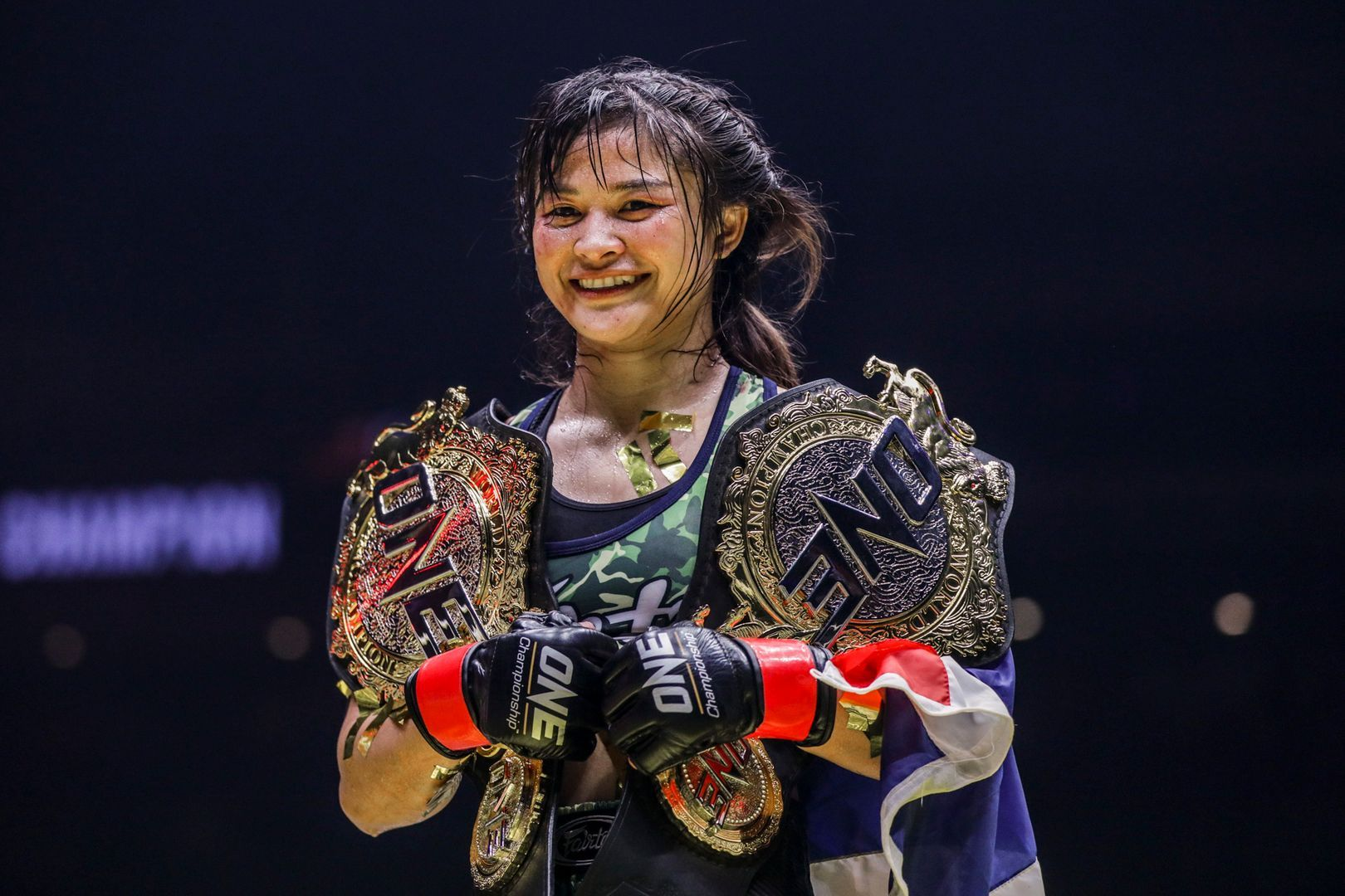 Stamp Fairtex with her ONE Atomweight Muay Thai and Kickboxing World Title belts