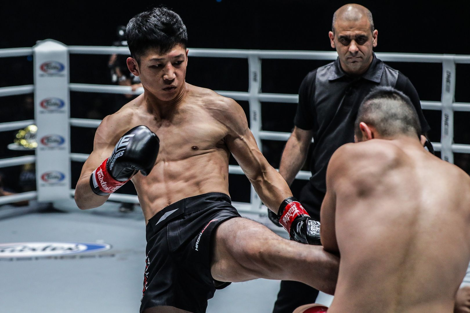 Japanese Muay Thai fighter Hiroki Akimoto throws a kick to Kenny Tse's gut
