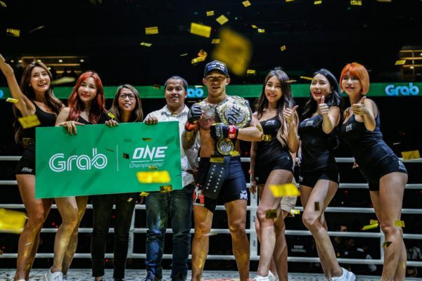 Martin Nguyen, ONE Featherweight World Champion, holds his World Title belt with the ONE ring girls.