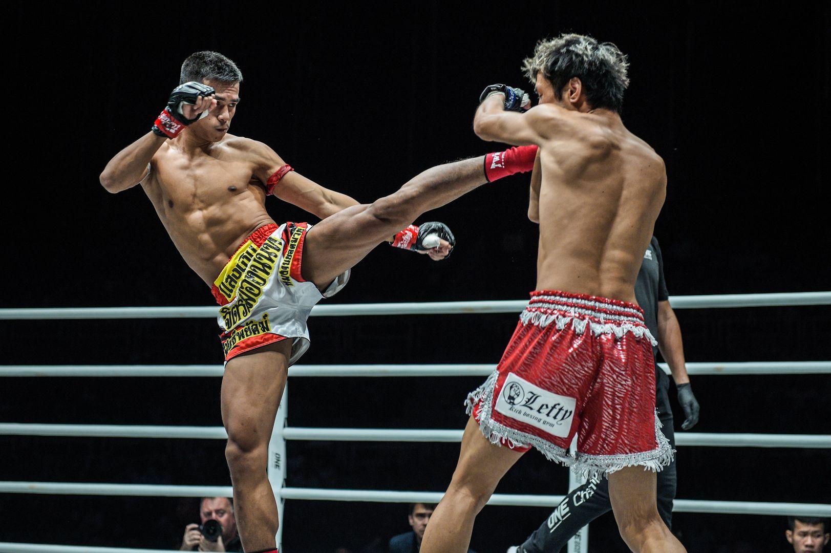 Muay Thai World Champion Panpayak Jitmuangnon blasts his rival with a roundhouse kick