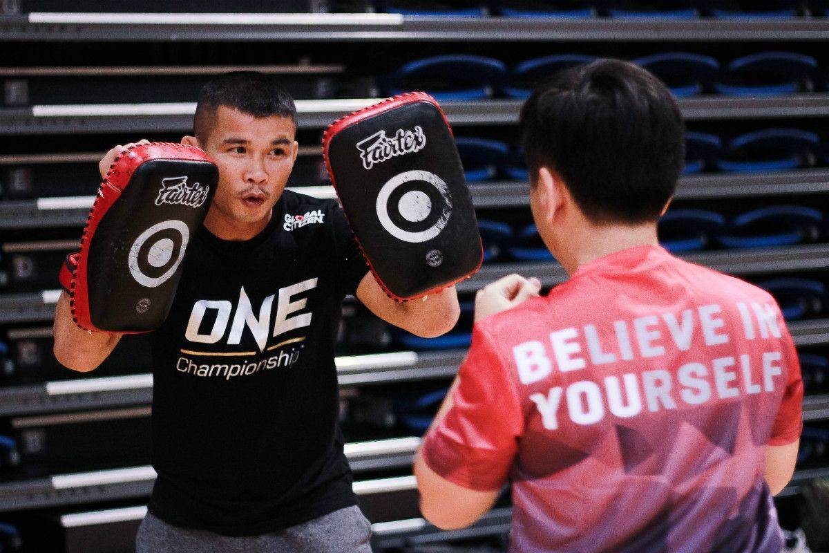ONE Bantamweight Muay Thai World Champion Nong-O Gaiyanghadao holds kick pads for a Singaporean youth
