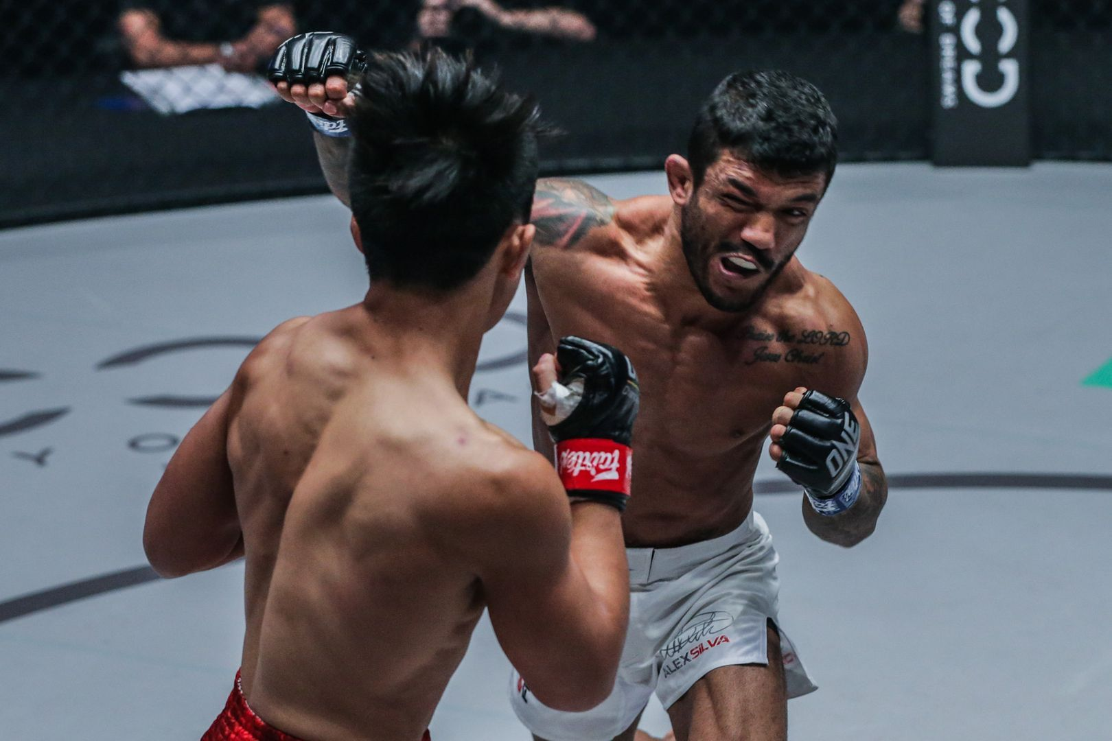 Brazilian mixed martial artist Alex Silva bites down on his mouthguard and hits Joshua Pacio