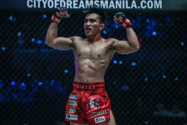 Joshua Pacio flexes after retaining his strawweight gold at ONE: FIRE & FURY.