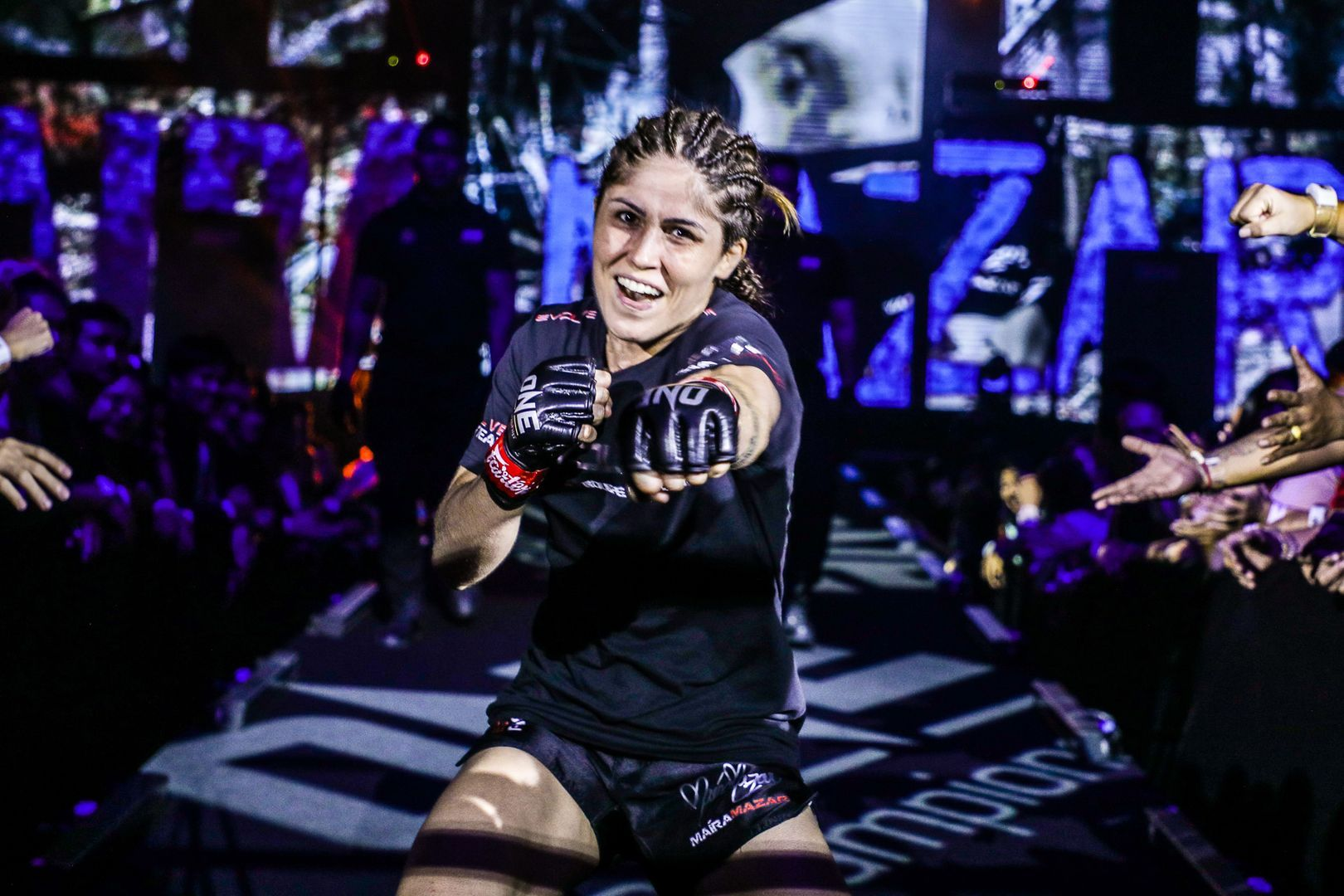 Brazilian MMA fighter Maira Mazar throws a punch on her way to the cage