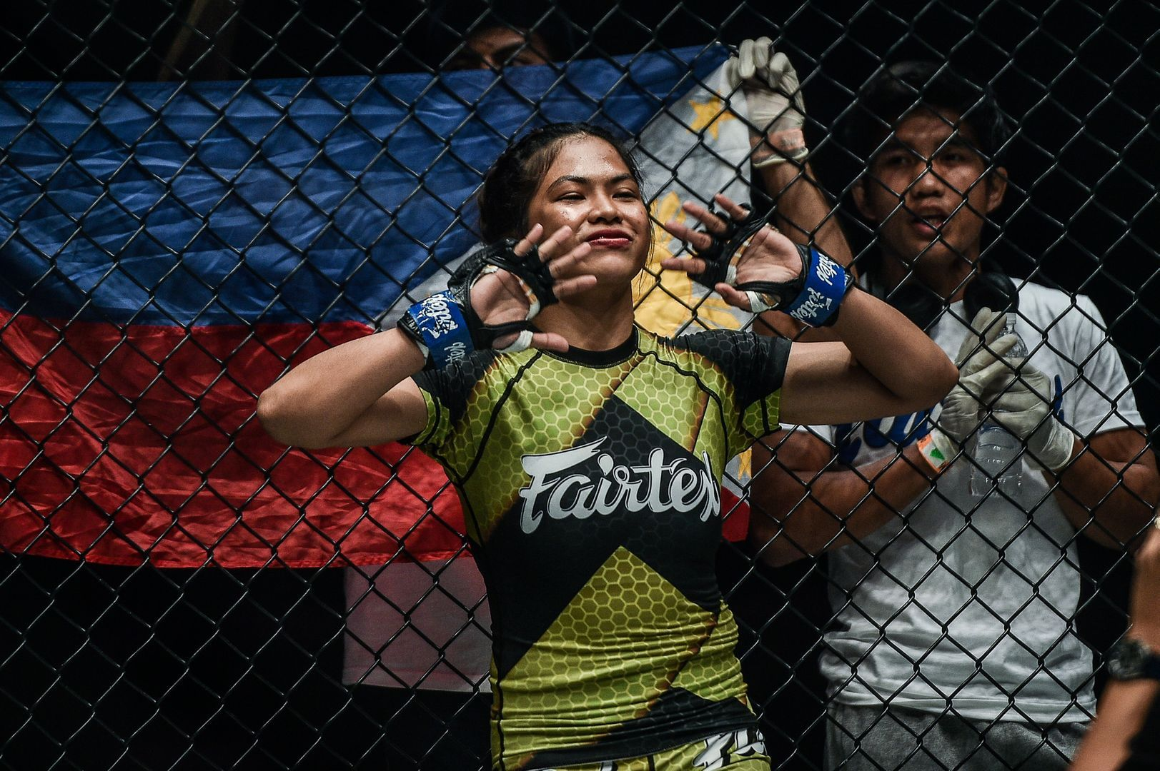 Philippine mixed martial artist stands against the fence
