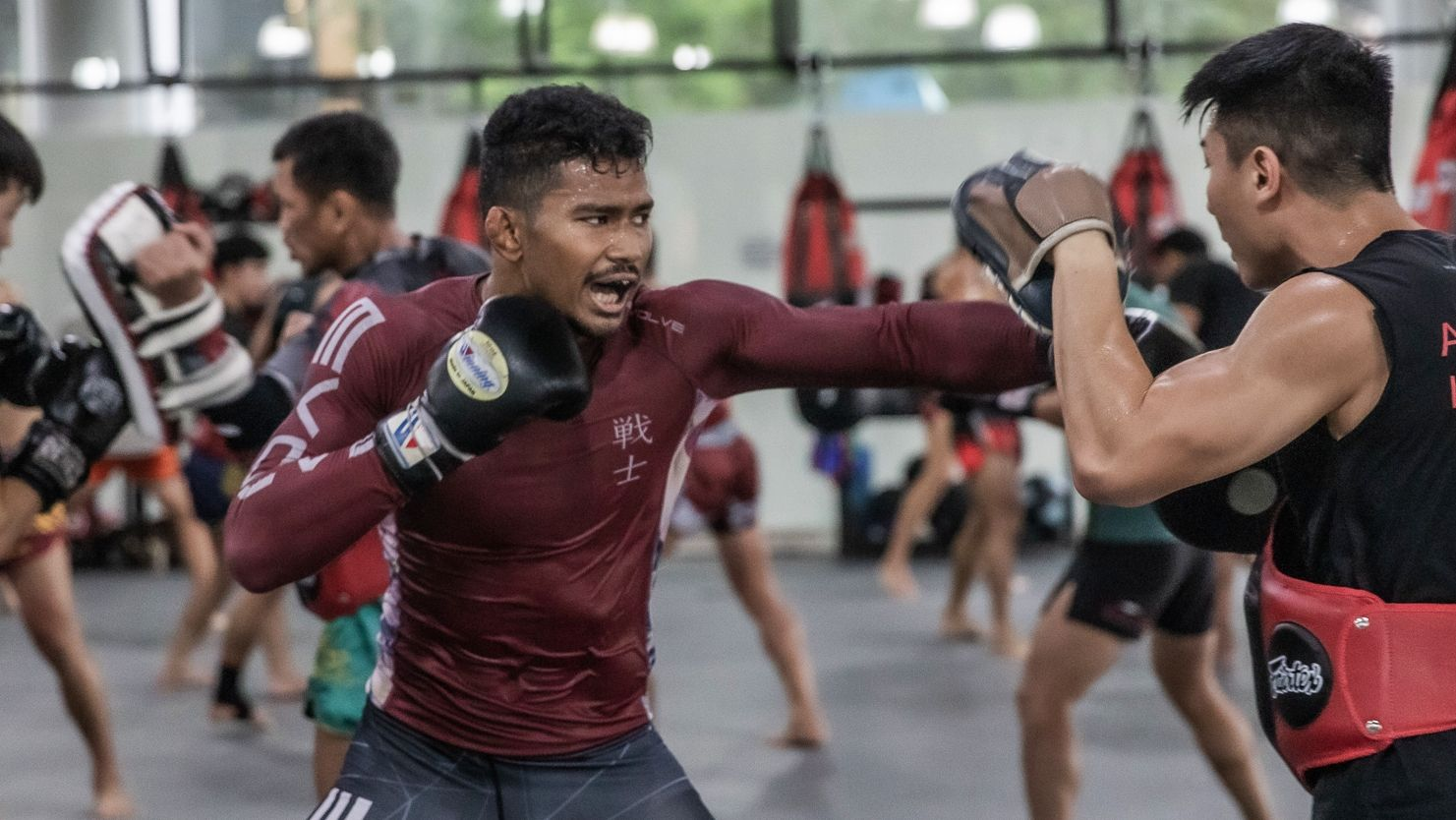 Amir Khan hits pads with his coach at Evolve MMA in Singapore