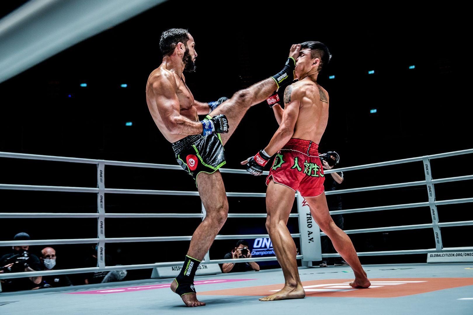 Tunisian striker Fahdi Khaled kicks Huang Ding in the face