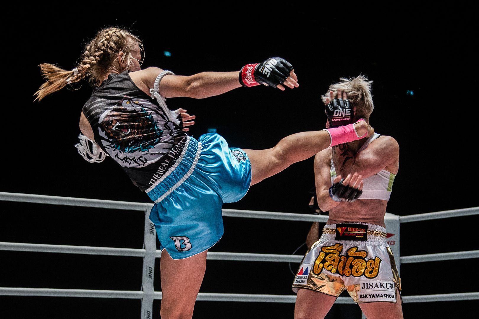 Marie Ruumet throws a head kick at Little Tiger