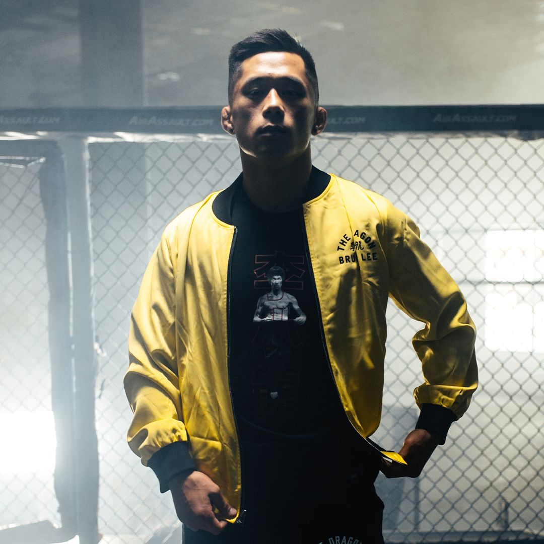 Martin Nguyen poses in the reversible bomber jacket from the ONE X Bruce Lee Collection from ONE.SHOP!