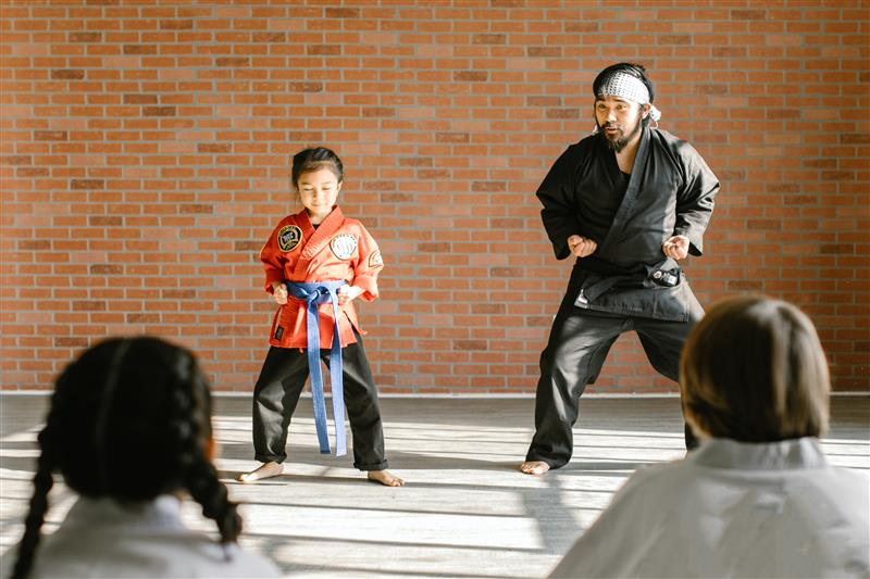 A martial arts instructor teaches a studen in class
