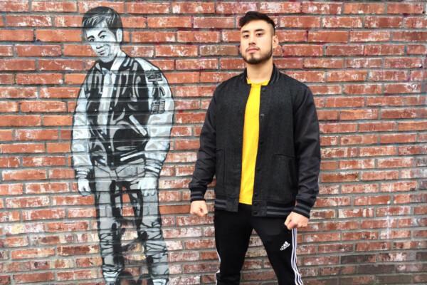 James Yang poses against a Bruce Lee mural