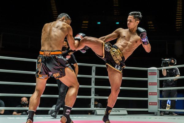 Thai kickboxer Superbon whips a kick at Sitthichai Sitsongpeenong's body