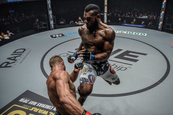 Brazilian MMA fighter Leandro Ataides leaps with a flying knee